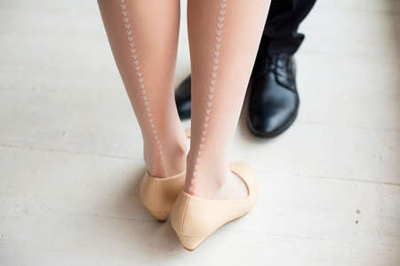 stocking feet: Female and male legs in rustic interior. Young woman dressed in cute white stockings with vertical line of little hearts drawing. Young couple in love standing together. Stock Photo