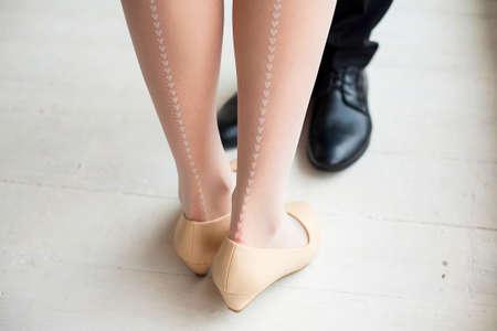 pies sexis: Piernas femeninas y masculinas en el interior rústico. mujer joven vestida con medias de color blanco lindo con la línea vertical de pequeños corazones de dibujo. Pareja joven en el amor de pie juntos.
