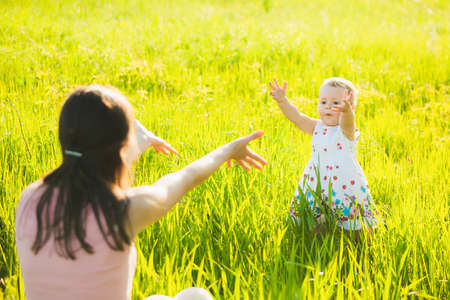 spring landscape: Little daughter happily running towards her mom. People having rest in sunny green meadow on spring or summer day. Mother and baby playing outside.