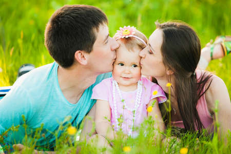 close portrait: Mom and dad kissing cheeks of little daughter. Family portrait.