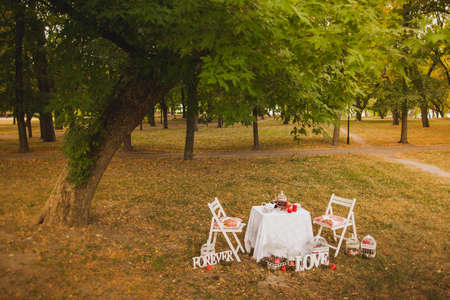 festively: Beautiful photobooth in autumn city park. Festively decorated white wooden chairs and table in scenic place. Image toned and stylized in retro style. Stock Photo