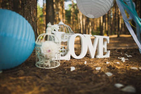Beautiful place for outside wedding ceremony in wood. Wedding settings. Love - wooden inscription. Festive stylish decor made by blue and white Japanese lanterns and many ribbons. Horizontal image. Stock Photo