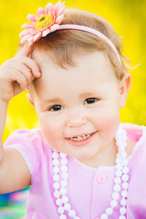 smilie: Close up portrait of charming smiley face of one year old small girl dressed in cute pink dress, white necklace and pink flower in hair. Happy child playing outside on spring or summer sunny day. Stock Photo