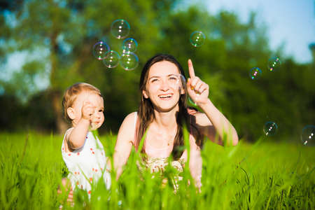 cheerfully: Family playing together outside. Mom and little daughter cheerfully catching soap bubbles. Portrait of happy joyful family of mum and child. Stock Photo