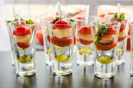 Small snacks canape with cherry tomatoes, cheese, olives on skewers