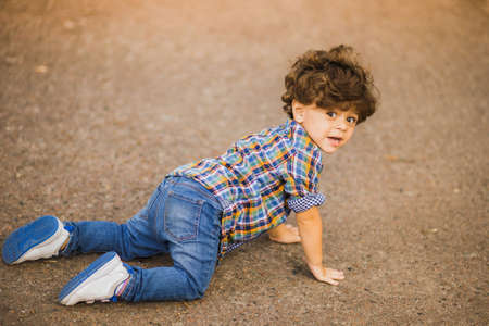 Boy playing outdoors, fell to his knees Stock Photo