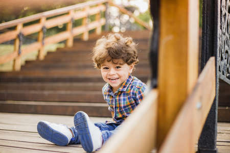 Portrait of little cute child sitting on wood stairs in city park. Boy looks at camera through wooden parapet of stairs