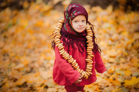 slavs: Child girl in Ukrainian folk scarf on head with floral print and with bunch of bagels on background of fallen leaves