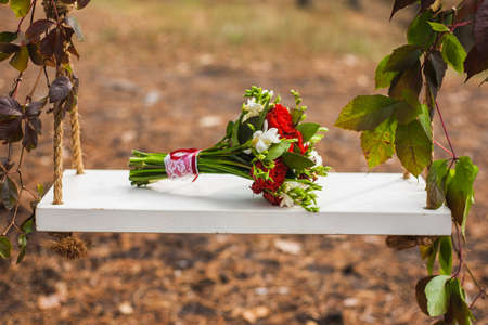 floristics: Beautiful swing, decorated ivy with bouquet red rose, element of a autumn wedding decor
