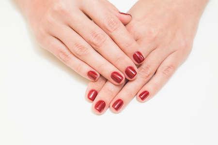 きらびやかな輝きと白い背景に分離されたプロの赤のマニキュアで白人の女性の手のクローズ アップ。ベースコートの最初とトップの治療法 UV また