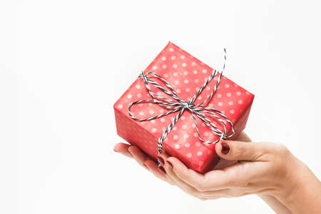Woman with beautiful red manicure holding small present in hands. Close up of box in wrapping paper isolated on white background. Horizontal color photo.