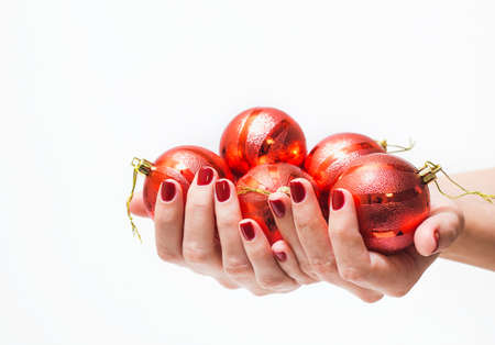 christmas manicure: Red round christmas ball in female hand isolated on white background. Close up of young woman hand with beautiful professional red manicure. Christmas celebration concept. Stock Photo