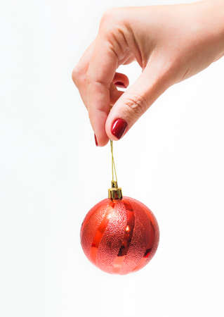 woman hanging toy: Red round christmas ball in female hand isolated on white background. Close up of young woman hand with beautiful professional red manicure. Christmas celebration concept. Stock Photo