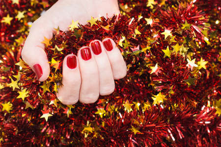 christmas manicure: Close up of caucasian female hands with professional red manicure with glittering sparkles isolated on Christmas background. Modern festive gel polish with base coat first and top cure with LED lamp