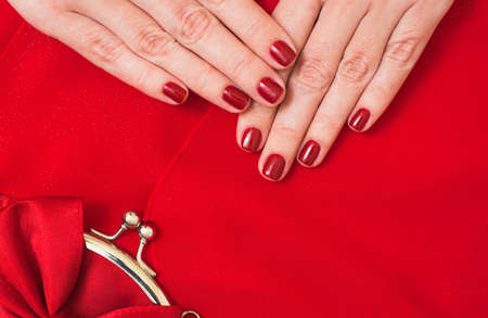 Beautiful small red female purse in hands of young woman and red evening dress. Accessory and clothes perfectly matching to each other. Fingernails with beautiful professional red manicure. Flat lay. Stock Photo
