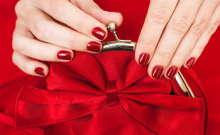 perfectly: Beautiful small red female purse in hands of young woman and red evening dress. Accessory and clothes perfectly matching to each other. Fingernails with beautiful professional red manicure. Flat lay. Stock Photo