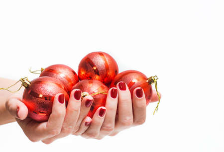 christmas manicure: Many red round christmas balls in female hands isolated on white background. Close up of young woman hands with beautiful professional red manicure. Christmas celebration concept. Stock Photo