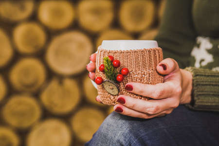christmas manicure: Cup of hot tea or coffee or cocoa in knitted vintage cup holder with christmas decorations in hands of woman with beautiful festive red manicure. Woman sitting in rustic interior. Horizontal photo Stock Photo