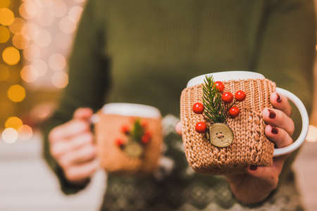 christmas manicure: Cups of hot tea or coffee or cocoa in knitted vintage cup holders with christmas decorations in hands of woman with beautiful festive red manicure. Woman proposing one cup into camera.