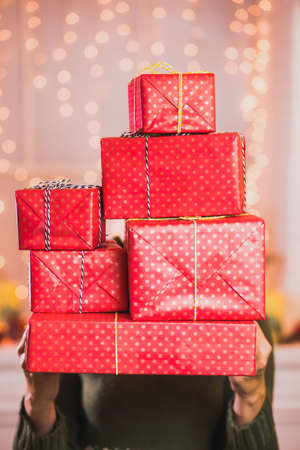 festively: Woman holding many beautiful present in red wrapping paper ready to put under Christmas tree. Woman decorating living room for xmas celebration for her family. Vertical color photo.