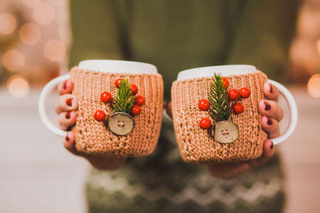 Cute winter Christmas mugs. Cups of hot tea or coffee or cocoa in knitted vintage cup holders with xmas decorations in hands of woman with festive red manicure. Woman holding cups together closely.