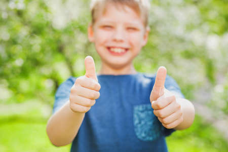 Handsome cheerful 9 years old boy giving two hands with thumbs up into camera as symbol of success. Closeup of fingers with focus at them and blurry face of blonde cute happy kid with great smile. Zdjęcie Seryjne