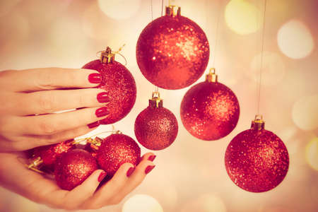 Close up of caucasian female hands with professional red manicure with glittering sparkles isolated on Christmas background holding New Year round balls ready to decorate tree Stock Photo