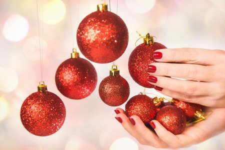 Close up of caucasian female hands with professional red manicure with glittering sparkles isolated on Christmas background. Woman holding New Year round balls ready to decorate tree