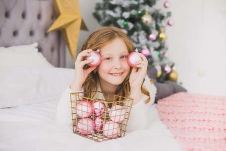 Portrait of cute happy little girl on Christmas morning in home interior. Child paying with holiday decorations, making eye of pink balls while laying on bed. Horizontal color photo