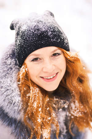 Portrait of beautiful young woman over winter snowy white background. Close up of female smiling face with gorgeous long ginger hair.