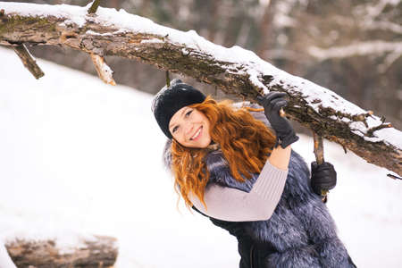 Portrait of smiling ginger winter girl looking cheerfully at camera. Closeup of beauty face of young woman in winter fur clothing outside at snowy cold winter day background.