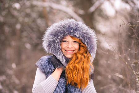 Portrait of smiling ginger winter girl looking cheerfully at camera. Closeup of beauty face of young woman in winter fur clothing outside at snowy cold winter day background Stock Photo