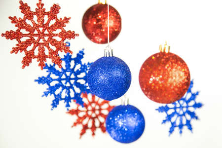 Beautiful Christmas and New Year colorful background. Close up of red and blue shining ornaments hanging on glossy silver ropes isolated on white. Horizontal color phtography.