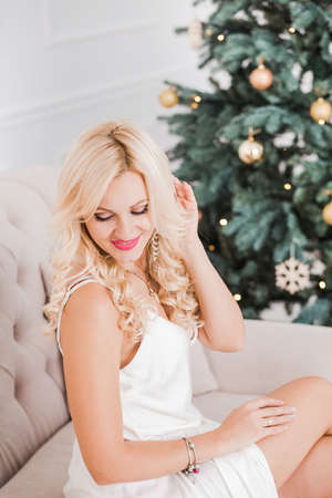 Portrait of beautiful young woman with long blond hair sitting on fair couch in holiday interior. View from above. Vertical color photography.