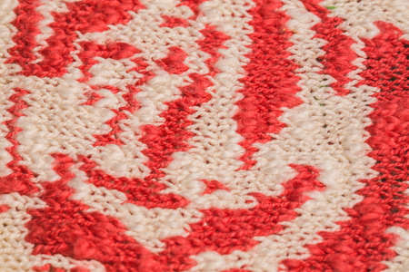 Macro color image of red and white knitted texture.