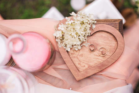 Closeup top view of two golden wedding rings on wooden heart background decorated with white small flowers.  Horizontal color photography.
