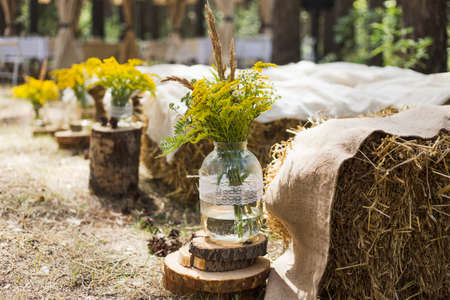 Beautifully decorated place in old autumn wood for wedding ceremony. Rustic style of elements of decor. Stok Fotoğraf