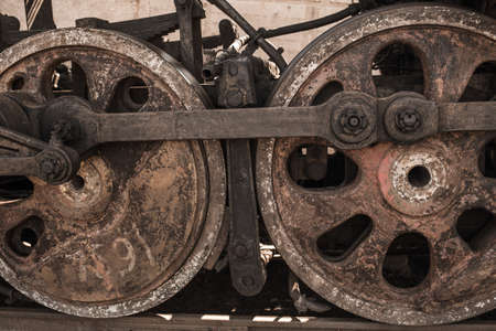 Closeup view of wheels of abandoned old rusty soviet locomotive at platform. Horizontal color photography.