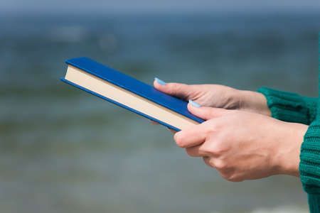 Closeup of white female hands  holding thick paper book in hands isolated at blurry blue sea background