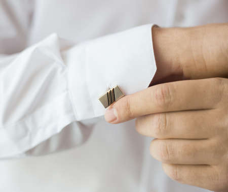 White man dressing up for oficial occasion. Closeup view of long sleeve of shirt and cufflink. Horizontal color photography.