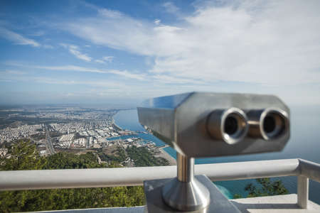 Metal grey coin operated telescope isolated at beautiful summer panoramic view at cityscape Banque d'images - 115399478