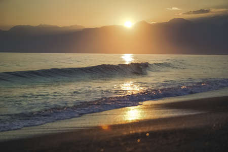 Golden evening splashing sea wave at sunset sky and soft sun light background Stock Photo