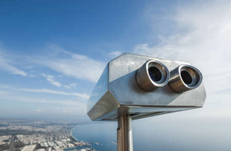 Metal grey coin operated telescope isolated at beautiful summer panoramic view at cityscape