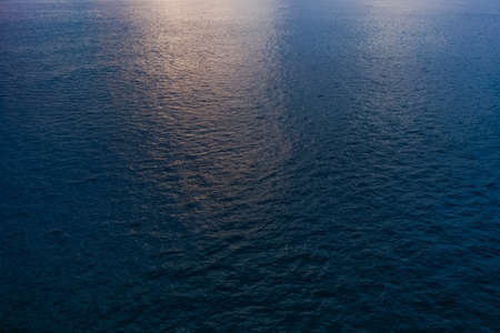 Blue sea water with soft reflection of sunset sun on calm surface. Nature background. Horizontal color photography.