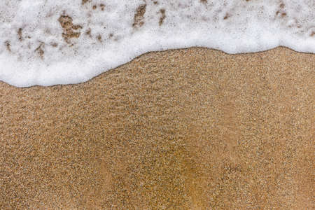 Top view of surface of clean golden sand at sea beach and white foamy wave. Horizontal color photography. Banque d'images - 115399852