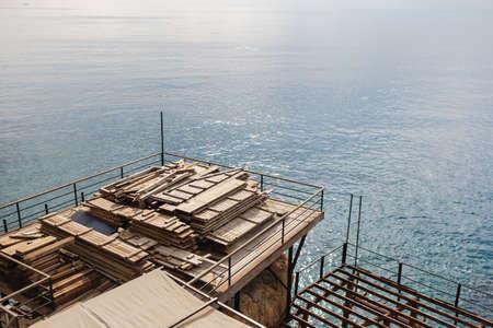 Finish of summer beach holidays season concept. Disassembled wooden pontoon at seashore. Preparations to winter cold season. Horizontal color photography. Imagens