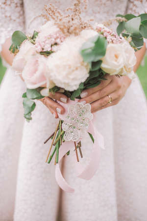 Closeup view of beautiful bridal hands holding perfect bridal bouquet of flowers. Focus at pink nude manicure with soft shimmering at nails of young woman. Vertical color photography.