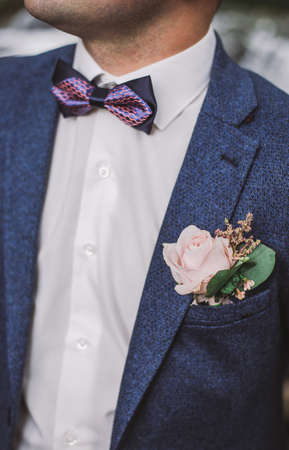 Close-up vertical color image of handsome groom wearing blue suit, white shirt, bowtie and boutonniere.