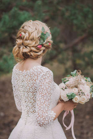 Closeup back view of beautiful blond bride standing outdoors in wood posing for wedding photoshoot. Pastel colors hairstyle decorated with fresh flowers. Vertical color photo.