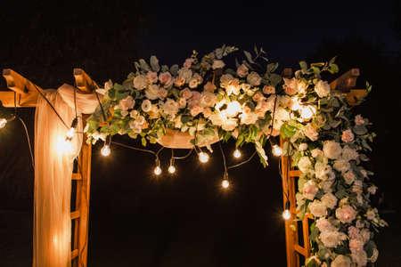 Hermoso lugar realizado con escuadra de madera y decoraciones florales para ceremonia de boda exterior en madera de noche. Fotografía en color horizontal.